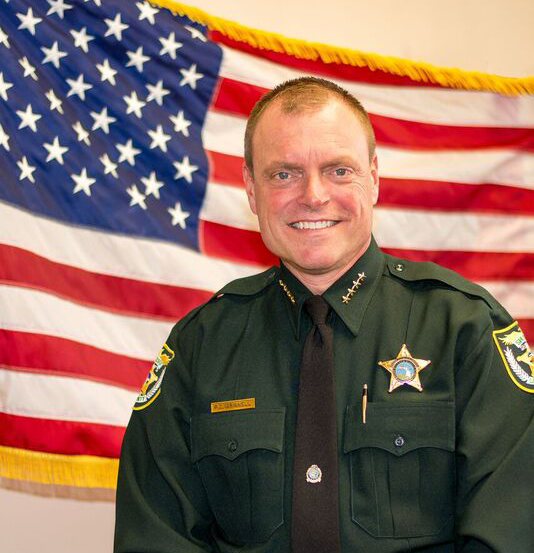 Picture of Sheriff Peyton C. Grinnell with American flag in background